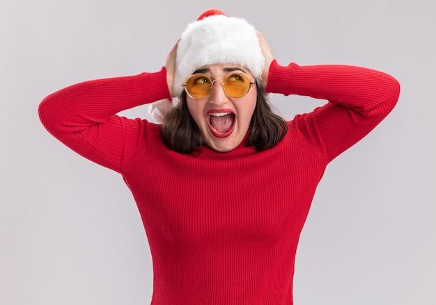 Молодая девушка в красном свитере и шляпе санта-клауса в очках кричит с раздраженным выражением лица, стоя на белом фоне