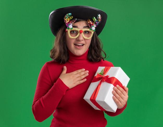 녹색 벽 위에 현재 놀라고 행복 서를 들고 재미 안경과 검은 모자를 쓰고 빨간 스웨터에 어린 소녀