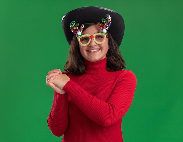 재미있는 안경과 함께 손을 잡고 검은 모자를 쓰고 빨간 스웨터에 어린 소녀 행복하고 긍정적 인 녹색 벽 위에 유쾌하게 서 웃고