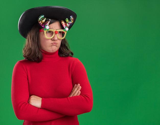 재미 있은 안경과 검은 모자를 쓰고 빨간 스웨터에 어린 소녀가 팔에 불쾌감을 느끼고 녹색 벽 위에 서있는 뺨을 불고 넘어