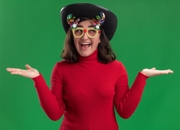 재미 있은 안경과 검은 모자를 쓰고 카메라를 행복하고 긍정적으로보고 빨간 스웨터에 어린 소녀