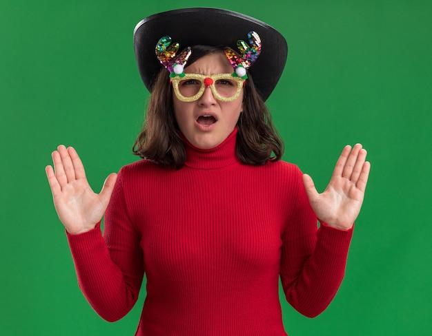 재미 있은 안경과 짜증이 표정으로 카메라를보고 검은 모자를 쓰고 빨간 스웨터에 어린 소녀