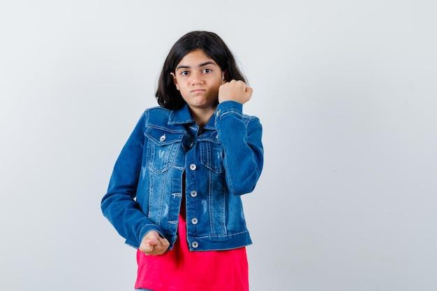 赤いtシャツとジーンズのジャケットの若い女の子は拳を握りしめ、真剣に見える、正面図。