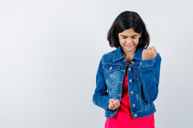 赤いtシャツとジージャンの若い女の子が拳を握りしめ、かわいく見える