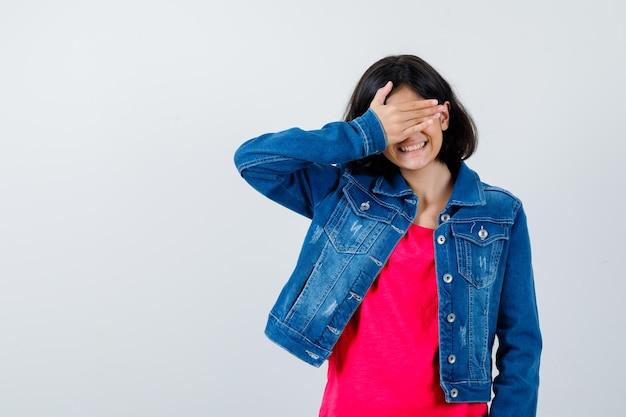 赤いtシャツとジーンズのジャケットを着た少女が手で目を覆い、かわいく見える、正面図。