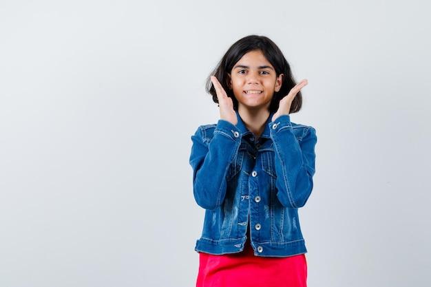 Молодая девушка в красной футболке и джинсовой куртке, держась за руки возле лица и выглядела веселой, вид спереди.