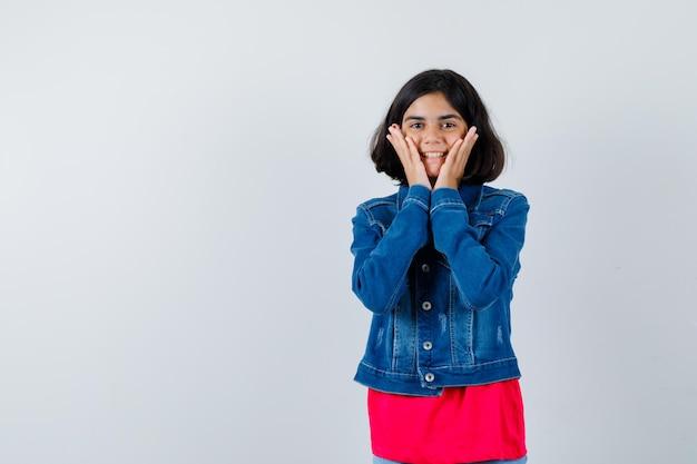 赤いtシャツとジーンズのジャケットの若い女の子が頬に手をつないで幸せそうに見える、正面図。