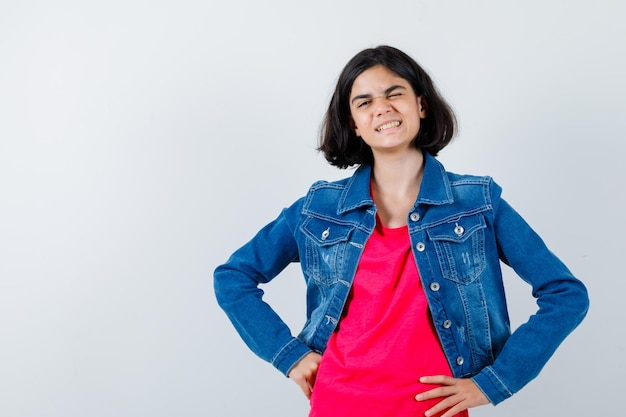 赤いtシャツとジーンズのジャケットで腰に手をつないで幸せそうに見える若い女の子