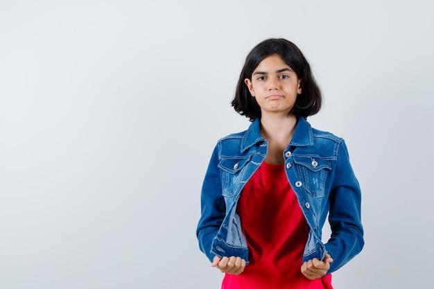 赤いtシャツとジーンズのジャケットを着た若い女の子が手でジャケットを保持し、真剣に見える、正面図。