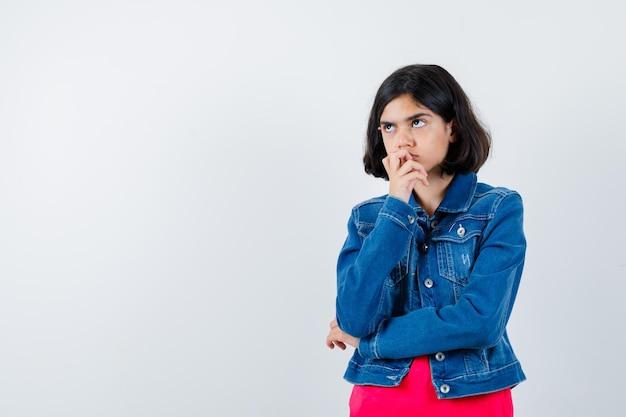 何かを考えて物思いにふける、正面図を探している間、手のひらに顎をもたれている赤いtシャツとジージャンの若い女の子。
