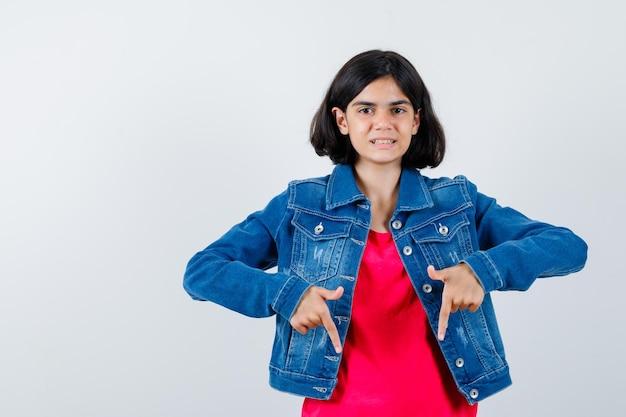 人差し指で下を向いて、かわいい、正面図を探している赤いtシャツとジージャンの若い女の子。