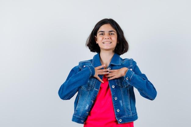 赤いtシャツとジーンズのジャケットを着た若い女の子が自分を指して幸せそうに見える、正面図。