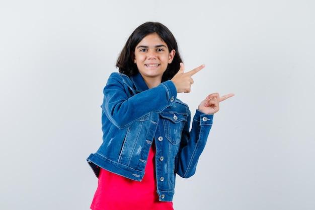 Молодая девушка в красной футболке и джинсовой куртке указывает вправо указательными пальцами и выглядит счастливой, вид спереди.