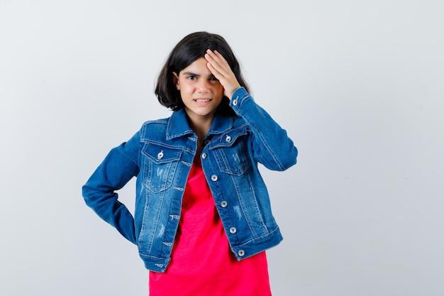빨간 티셔츠와 진 재킷을 입은 어린 소녀가 이마에 손을 얹고 허리에 손을 대고 짜증을 내며 정면을 바라보고 있습니다.