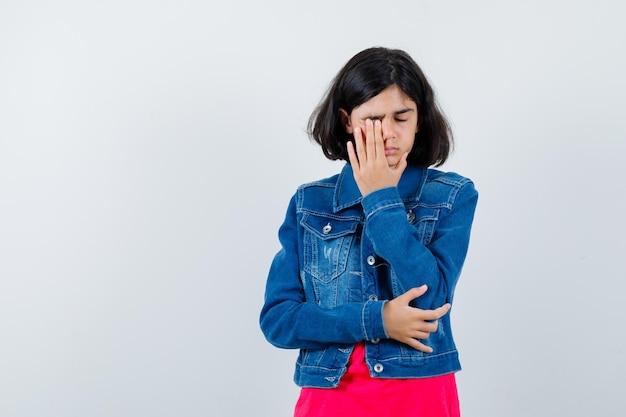 빨간 티셔츠와 진 재킷을 입은 어린 소녀가 눈을 비비고 피곤해 보이는 앞모습.