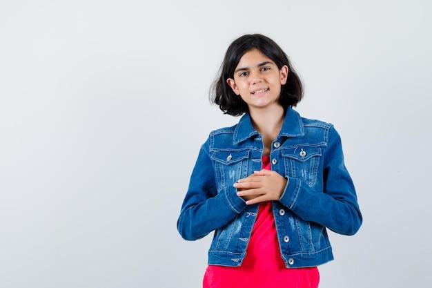 빨간 티셔츠와 진 재킷을 입은 어린 소녀가 손을 문지르고 쾌활한 앞모습을 보고 있습니다.