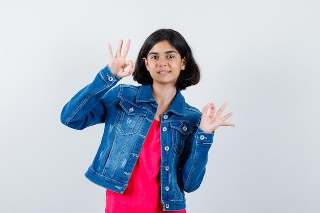 빨간 티셔츠와 진 재킷을 입은 어린 소녀가 확인 표시를 하고 행복해 보이는 앞모습을 보여줍니다.