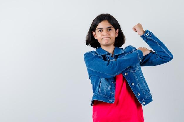 Молодая девушка в красной футболке и джинсовой куртке демонстрирует жест власти и выглядит мощно, вид спереди.