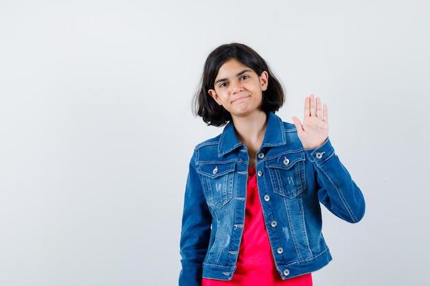 Молодая девушка в красной футболке и джинсовой куртке показывает знак остановки и выглядит жизнерадостной, вид спереди.
