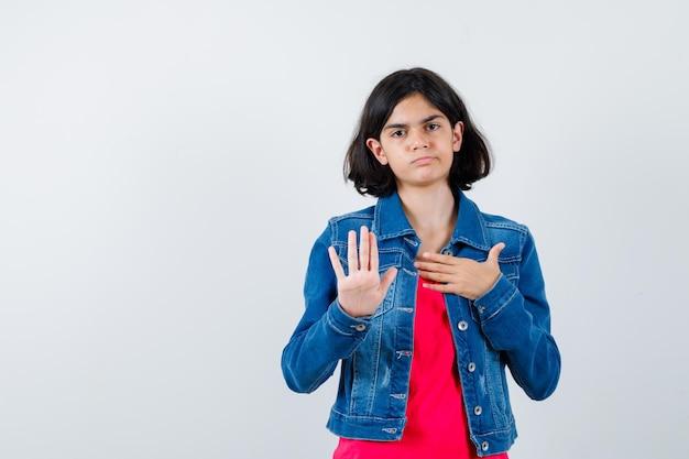 Молодая девушка в красной футболке и джинсовой куртке показывает знак остановки и выглядит серьезным, вид спереди.