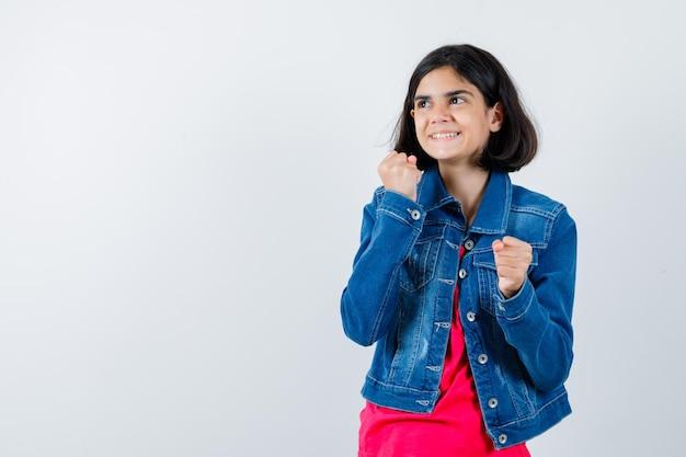 빨간 티셔츠와 진 재킷을 입은 어린 소녀가 복서 포즈를 취하고 행복해 보이는 앞모습을 보고 있습니다.