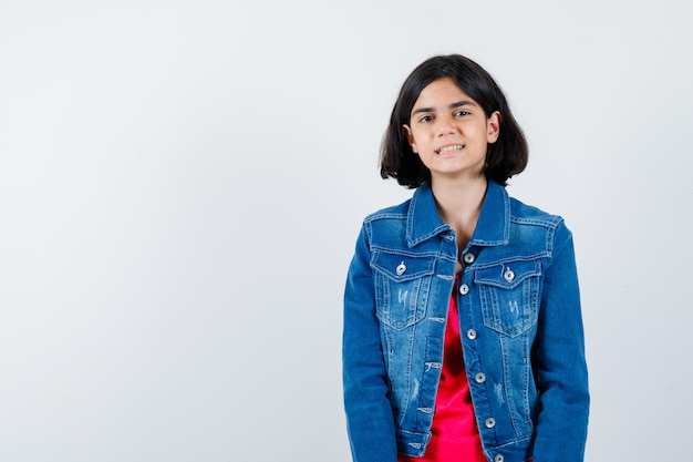 Молодая девушка в красной футболке и джинсовой куртке стоит прямо и позирует перед камерой и выглядит счастливой