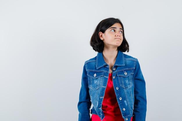 赤いtシャツとジージャンの若い女の子がまっすぐ立って、目をそらし、カメラに向かってポーズをとって、物思いにふける、正面図を見てください。