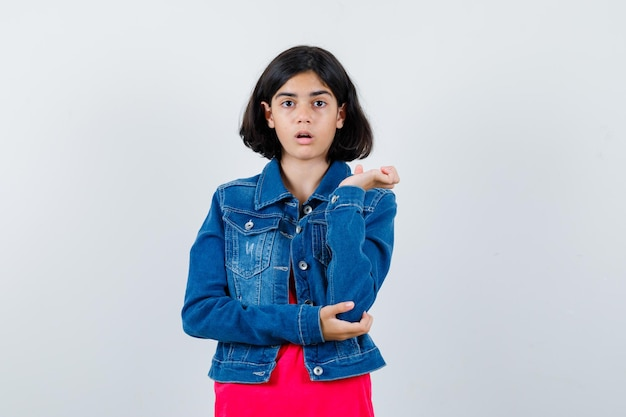 빨간 티셔츠와 진 재킷을 입은 어린 소녀가 뭔가를 들고 놀란 표정으로 손을 뻗고 있는 모습입니다.