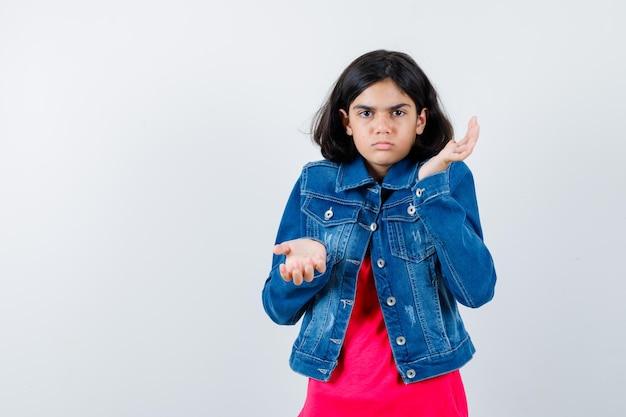 赤いtシャツとジーンズのジャケットを着た若い女の子が疑わしい方法で手を伸ばし、困惑した様子で、正面図。