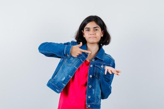 빨간 티셔츠와 진 재킷을 입은 어린 소녀가 한 손으로 무언가를 잡고 집게 손가락으로 가리키며 행복해 보이는 앞모습입니다.