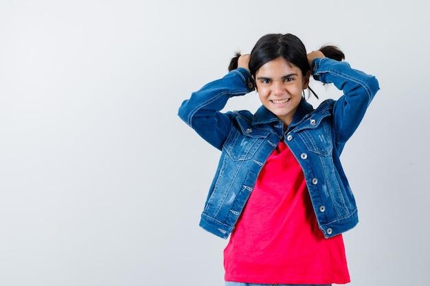 赤いtシャツとジーンズのジャケットの若い女の子が両手で髪を押し込んで幸せそうに見える、正面図。