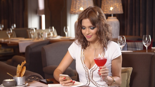 レストランのセクシーなワインを飲むの少女。
