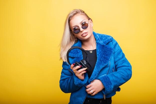 노란색에 파란색 세련된 재킷에 헤드폰 라운드 빈티지 선글라스에 어린 소녀