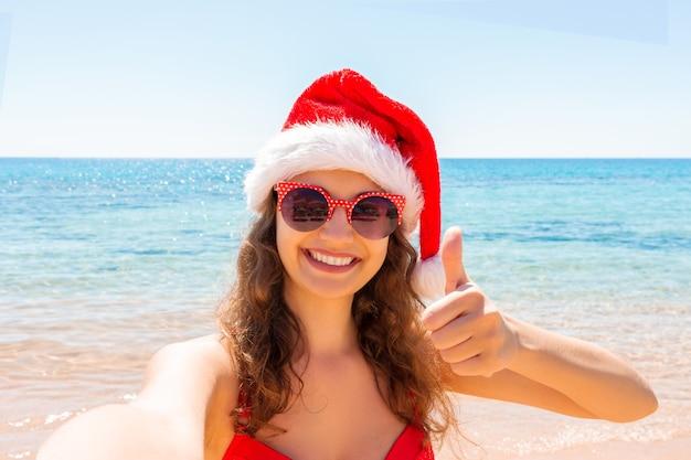 산타 모자에있는 어린 소녀가 자신의 스마트 폰 셀카 사진을 찍는 재미를 보여주는 엄지 손가락을 보여줍니다.