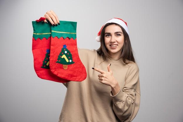 두 크리스마스 양말 가리키는 산타의 모자에 어린 소녀.