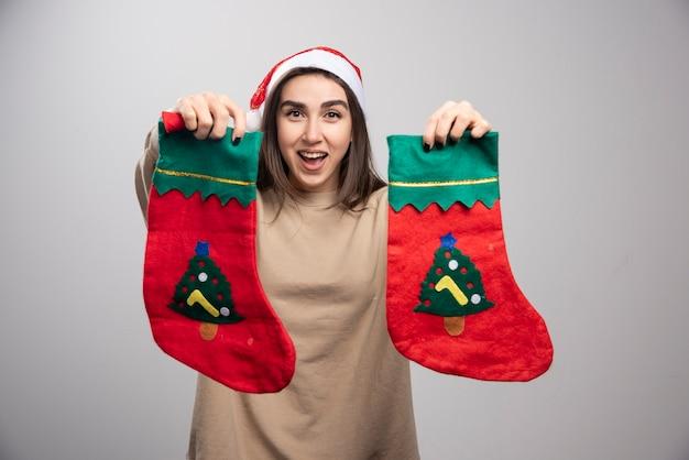 두 크리스마스 양말을 보여주는 산타의 모자에 어린 소녀.