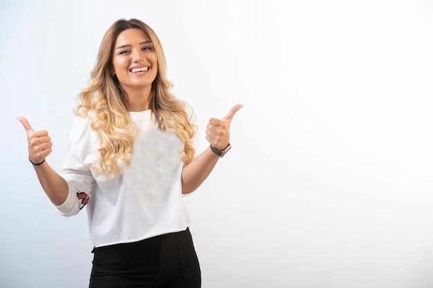 Молодая девушка в спортивной одежде делает большой палец вверх
