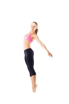 Молодая девушка в спортивной одежде прыгает и растягивается на белом фоне