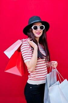 선글라스와 쇼핑백 모자에 어린 소녀