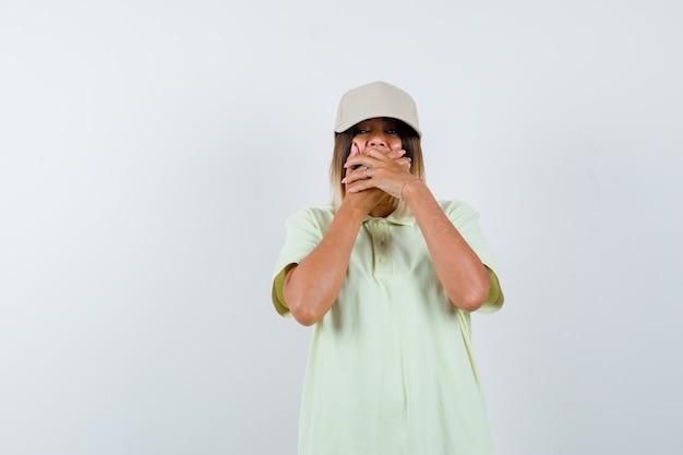 T- 셔츠와 모자에 손으로 입을 덮고 놀란, 전면보기를보고 어린 소녀.