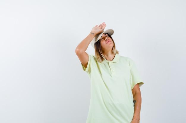 T- 셔츠와 모자 이마에 손을 잡고, 눈을 감고 유지 하 고 지쳐, 전면보기에 어린 소녀.