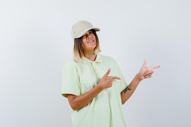 T- 셔츠와 모자 바로 검지 손가락으로 가리키고 귀여운, 전면보기를 찾고있는 어린 소녀.