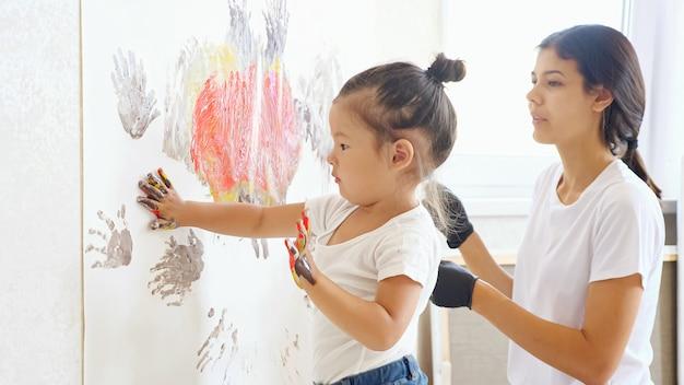 티셔츠와 청바지를 입은 어린 소녀는 밝은 창문을 배경으로 스튜디오에 손을 들고 큰 흰색 캔버스에 그림을 그리는 어머니와 함께 놀고 있습니다.