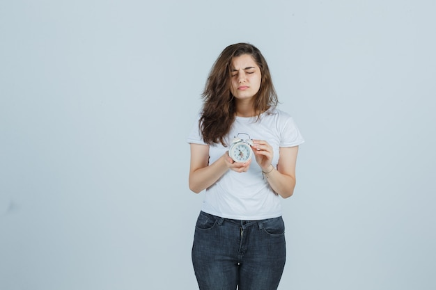 Молодая девушка в футболке, джинсах держит будильник, закрывая глаза и задумчиво, вид спереди.