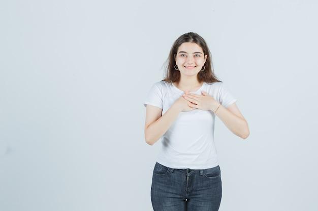 Молодая девушка в футболке, джинсах, взявшись за руки на груди и выглядя счастливыми, вид спереди.