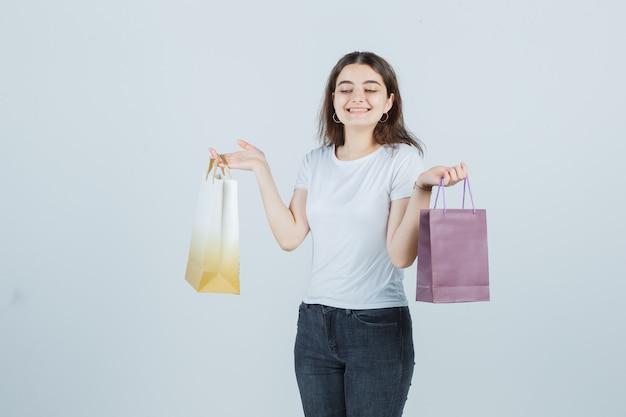 Молодая девушка в футболке, джинсах держит подарочные пакеты и выглядит счастливой, вид спереди.
