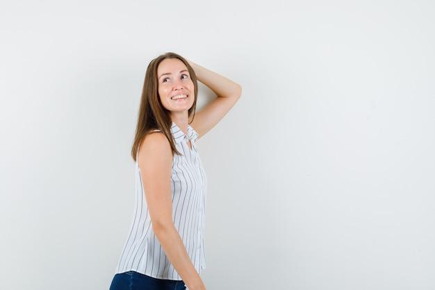 Молодая девушка в футболке, джинсах позирует с рукой на голове и выглядит радостной.