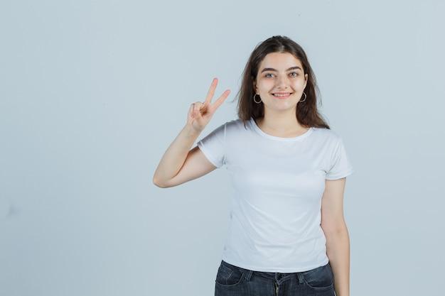 T- 셔츠, 청바지 승리 기호를 표시 하 고 행운, 전면보기를 찾고있는 어린 소녀.