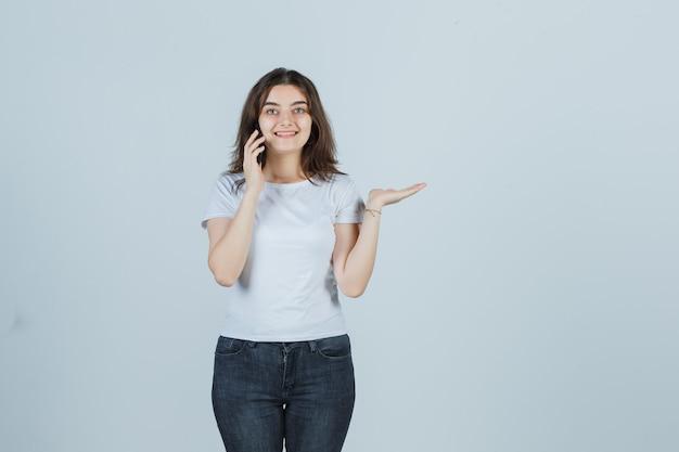Молодая девушка в футболке, джинсах разговаривает по мобильному телефону, делая вид, что держит что-то и выглядит счастливым, вид спереди.
