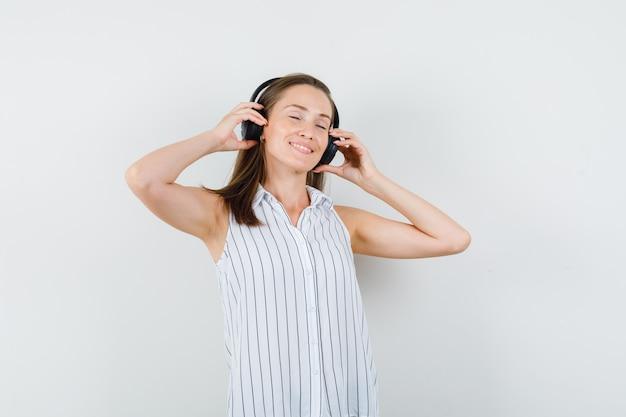 Молодая девушка в футболке, слушать музыку в наушниках и смотреть в восторге, вид спереди.